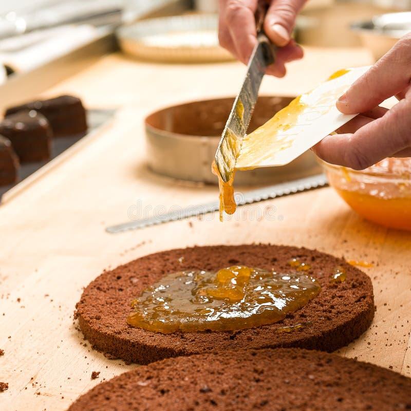 Cozinheiro que faz o bolo de chocolate da camada com doce de fruta foto de stock royalty free