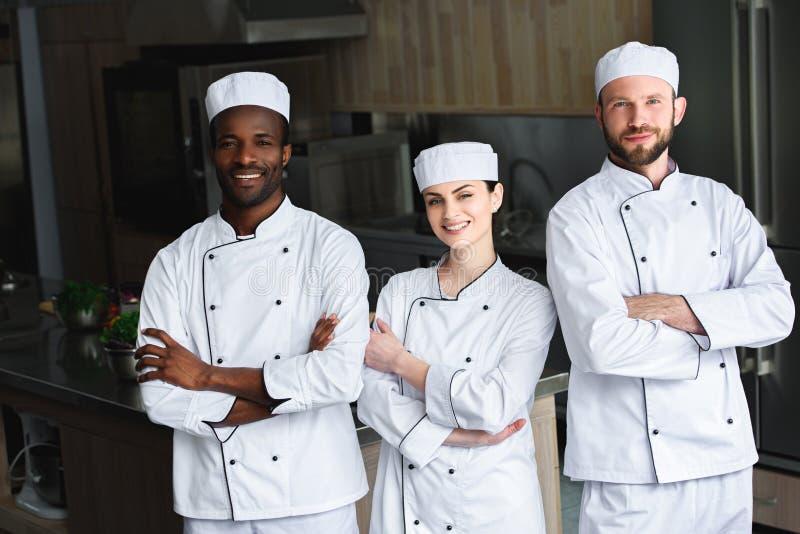 cozinheiros chefe multiculturais de sorriso que estão com braços cruzados fotografia de stock royalty free