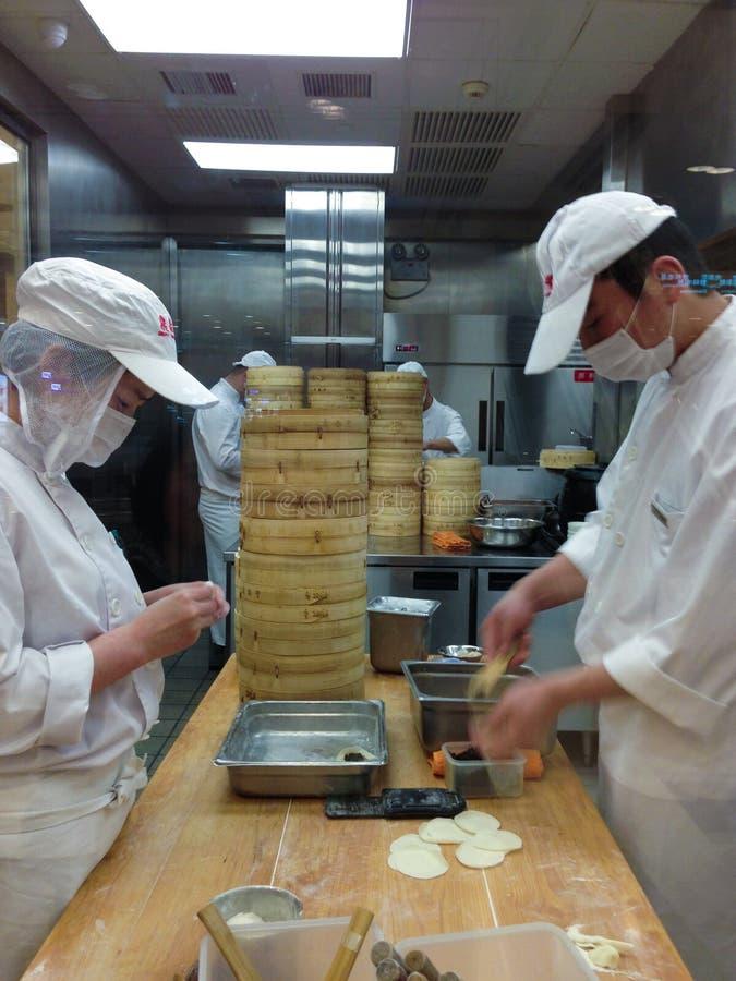 Cozinheiros chefe no trabalho em uma cozinha chinesa do restaurante imagem de stock royalty free
