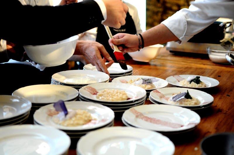 Cozinheiros chefe ocupados em um restaurante que arranja e que decora o alimento delicioso glamoroso em uma tabela de madeira par foto de stock royalty free