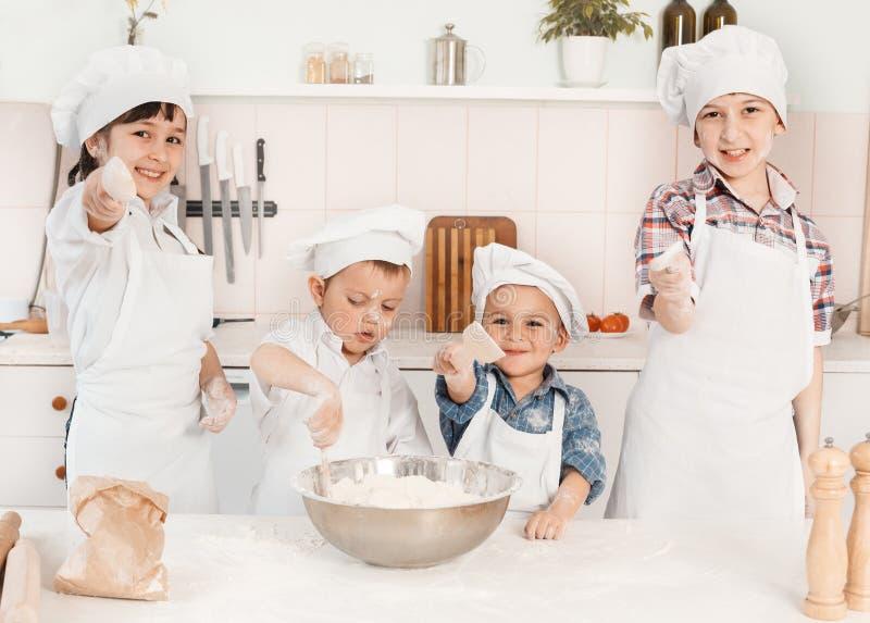 Cozinheiros chefe pequenos felizes que preparam a massa na cozinha fotografia de stock royalty free
