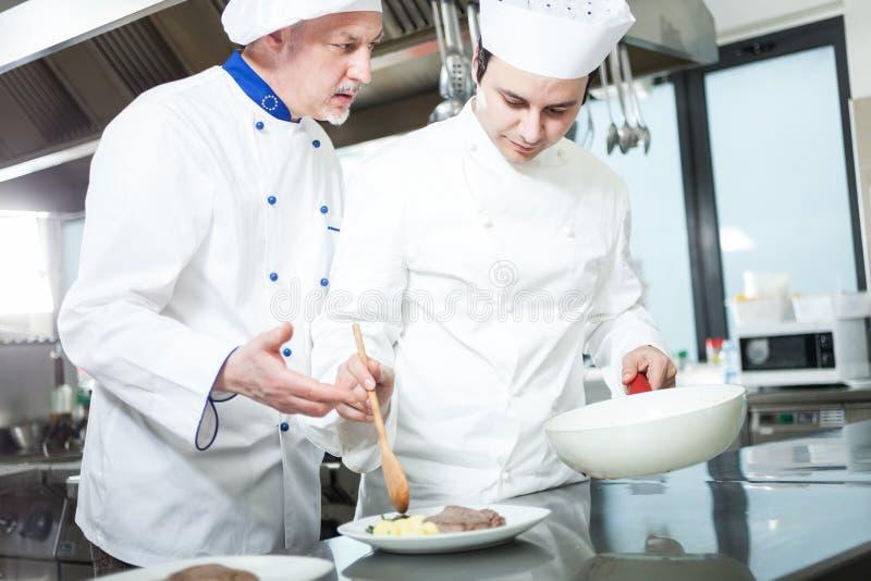 Cozinheiros chefe profissionais no trabalho imagem de stock