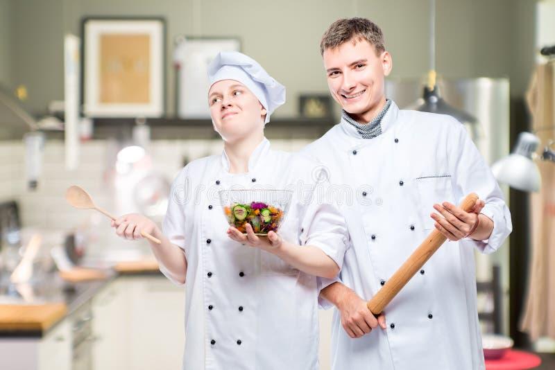 cozinheiros chefe profissionais novos emocionais com um prato no fundo imagem de stock