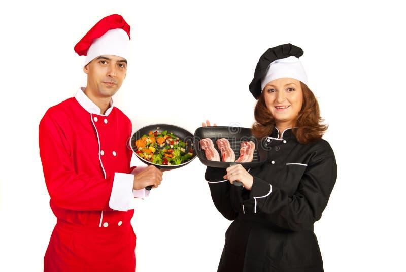 Cozinheiros chefe que mostram frigideiras imagens de stock royalty free