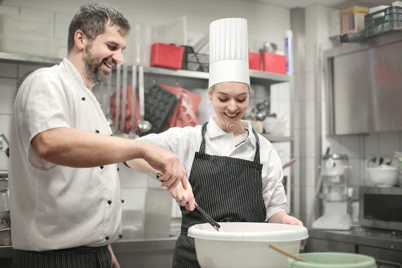 Cozinheiros que preparam uma refeição fotos de stock royalty free
