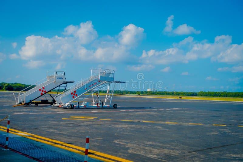 COZUMEL, MEXICO - NOVEMBER 12, 2017: Openluchtmening van twee die het inschepen treden in de Internationale baan van Cozumel word stock afbeelding
