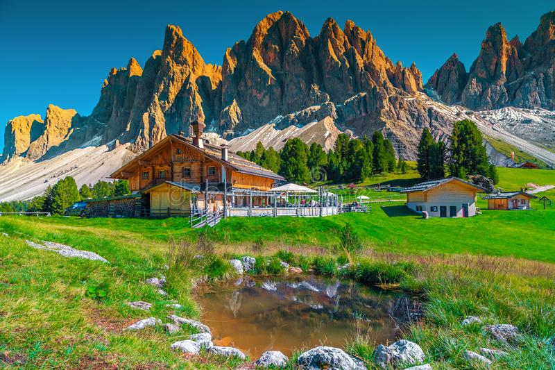 Cozy alpine chalets with mountain lake in Dolomites, Italy, Europe. Beautiful spring alpine landscape, mountain chalets and small lake with high snowy mountains stock images
