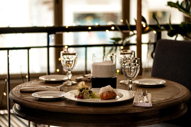 Cozy atmosphere at restaurant table with light snacks, cutlery and  glasses royalty free stock images