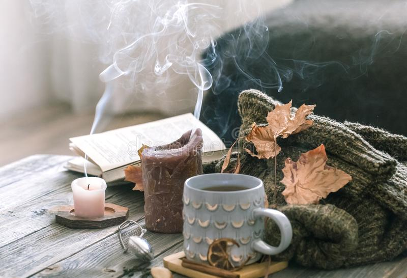 Cozy autumn morning breakfast in bed still life scene. Steaming cup of hot coffee, tea standing near window. Fall stock photo