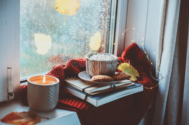 Cozy autumn morning at home. Hot cocoa with marshmallows and candle on window in rainy cold day stock image
