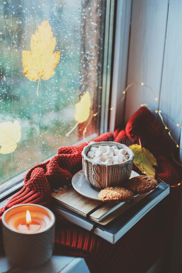 Cozy autumn morning at home. Hot cocoa with marshmallows and candle on window in rainy cold day. Spending holidays at home stock photography