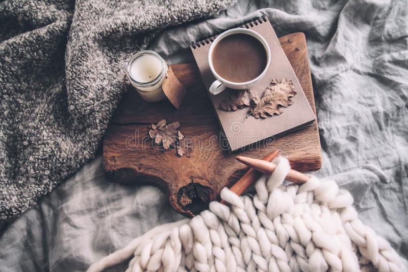 Cozy autumn weekend. Cup of coffee and candle on rustic wooden serving tray in the cozy bed with blanket. Knitting warm woolen sweater in the autumn weekend, top stock images