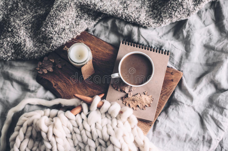 Cozy autumn weekend. Cup of coffee and candle on rustic wooden serving tray in the cozy bed with blanket. Knitting warm woolen sweater in the autumn weekend, top stock image