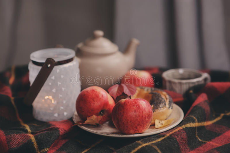 Cozy autumn weekend morning at home. Breakfast with cup of tea and bagel with apples. On woolen plaid blanket royalty free stock photo