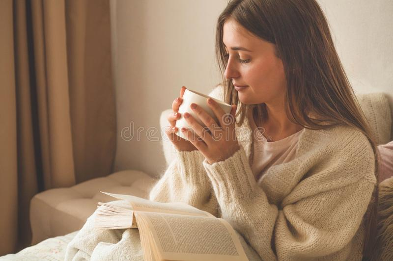 Cozy Autumn winter evening. Woman drinking hot tea and relaxing at home. Comfy lifestyle stock photography