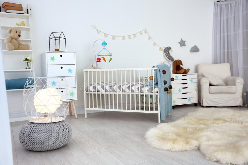 Cozy baby room interior with crib. And armchair stock photo