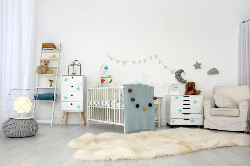 Cozy baby room interior with crib. And armchair stock images