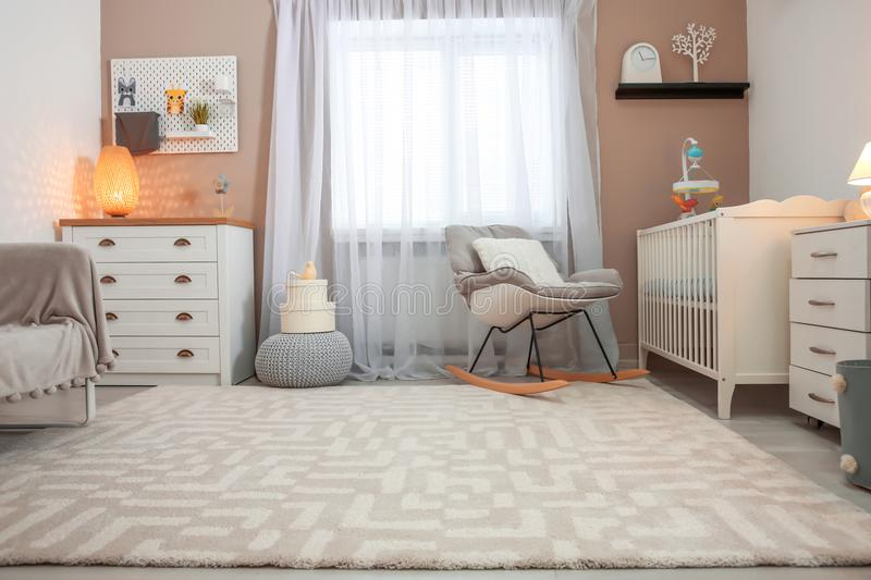 Cozy baby room interior with crib. And rocking chair royalty free stock photo
