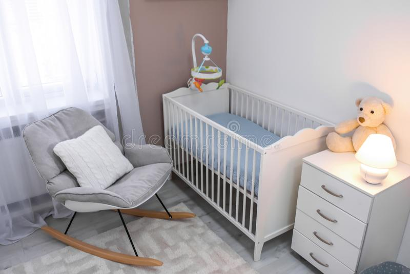 Cozy baby room interior with crib. And rocking chair stock images