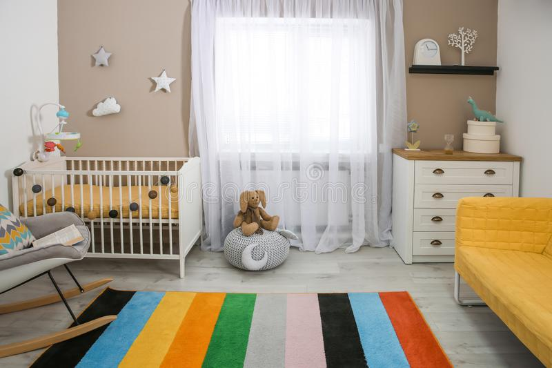 Cozy baby room interior with crib. And rocking chair royalty free stock images