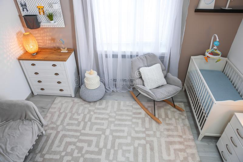 Cozy baby room interior with crib. And rocking chair royalty free stock photos