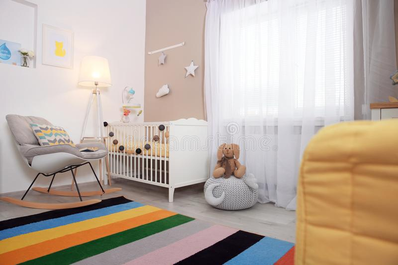 Cozy baby room interior with crib. And rocking chair stock photos