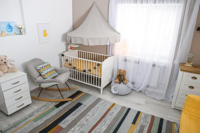 Cozy baby room interior with crib. And rocking chair stock photography