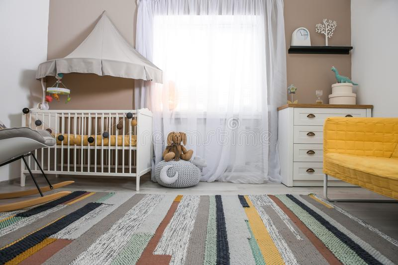 Cozy baby room interior with crib. And rocking chair royalty free stock image