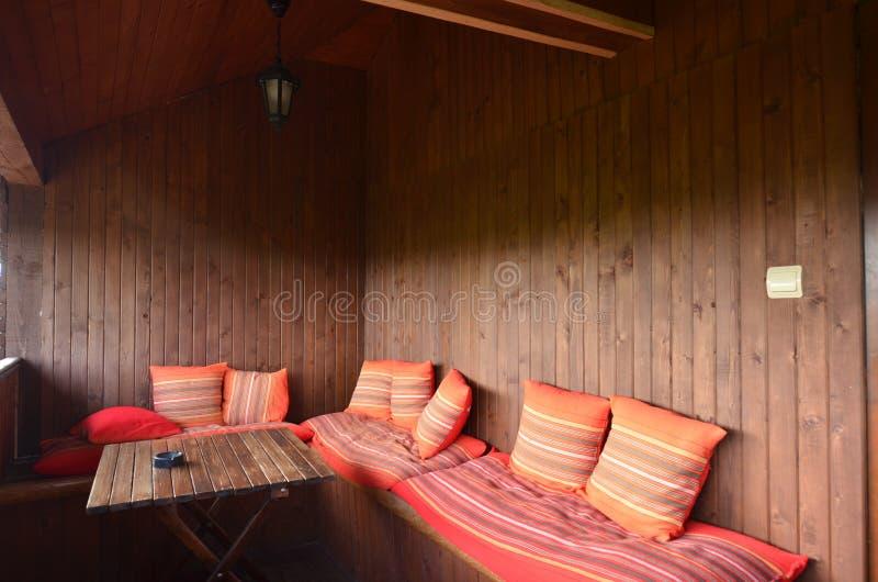 Cozy balcony in wooden house. Cozy comfortable balcony in pension house. Wooden walls and table, pillows stock photo