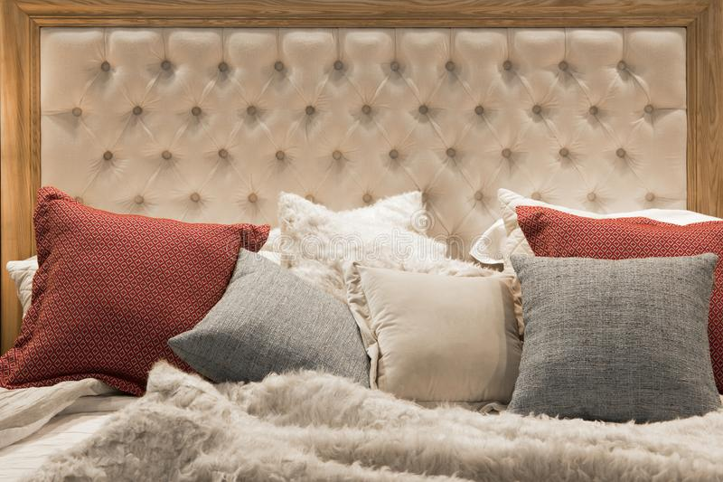 Cozy bed with quilted leather headboard in a wooden frame in beige and brown colors and pastel pillows stock photos