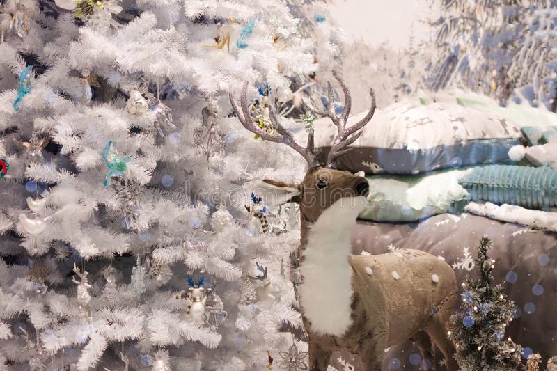 Cozy bedroom interior decorated with Christmas details: soft deer toy, Christmas tree, branches at the wall near bed with snow royalty free stock photos