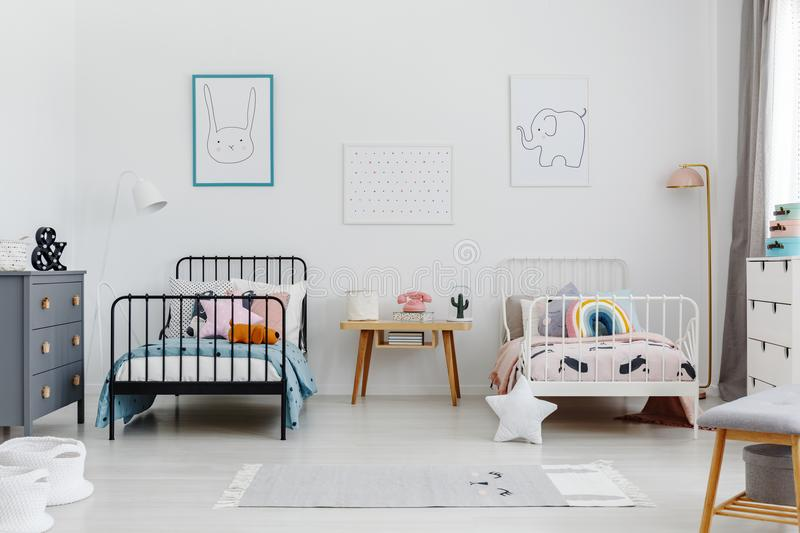 Cozy bedroom interior for siblings. Two beds, one white, one black with patterned bedding and posters of a rabbit and elephant on stock image