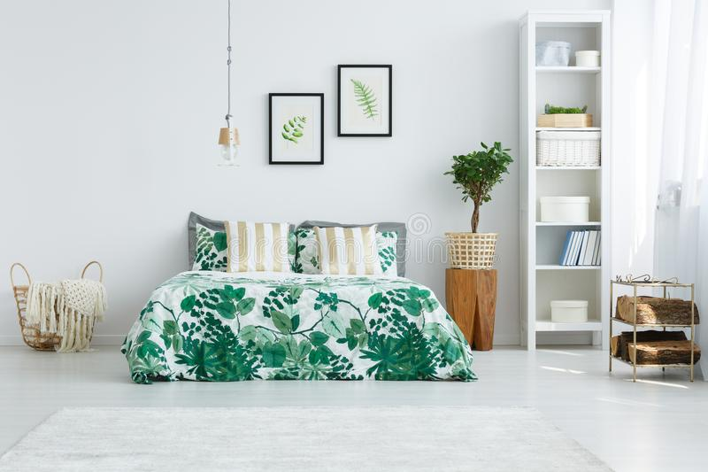 Cozy bedroom with small tree. Striped gold pillows on bed with green quilt in cozy bedroom with small tree on wooden stool and knit blanket in basket stock images