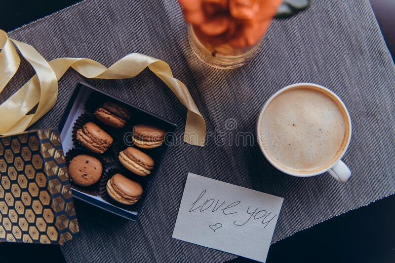 Cozy breakfast for lover. Romantic morning in noir nordic style. Coffee cup, box with macaroons, greeting card with handwrite Love. You words on gray napkin stock photo