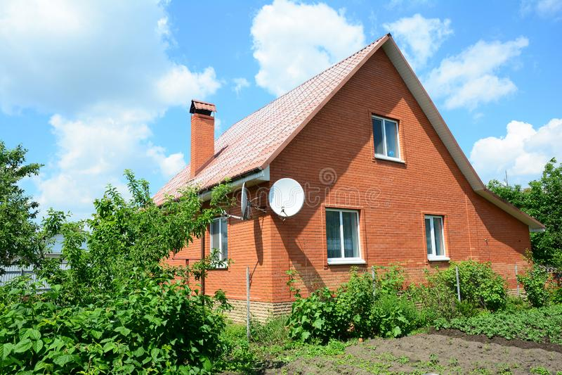 Cozy brick house with antenna and metal roof stock photo