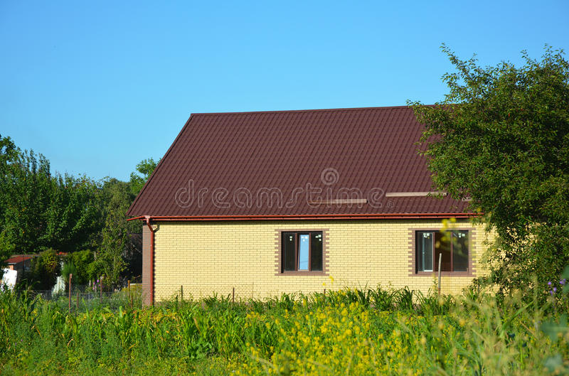 Cozy brick house with metal roof exterior. Suburban house. royalty free stock photo