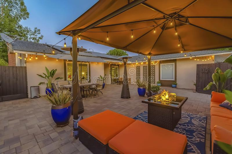 Cozy brick patio of a home with colorful seating area under a pavilion. A dining area under an umbrella can be seen near the house and brown wooden gate stock photo