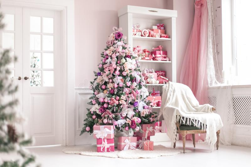 Cozy bright children`s room with Christmas tree, chair and toys. Selective focus. royalty free stock image