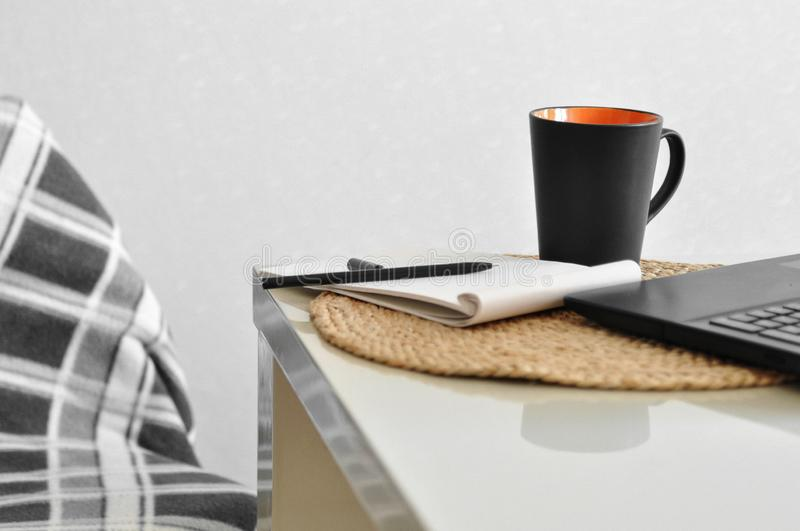 A cozy chair with a blanket and a laptop, cup of coffee, note, pen on a white kitchen table. Online shopping and freelance stock photography