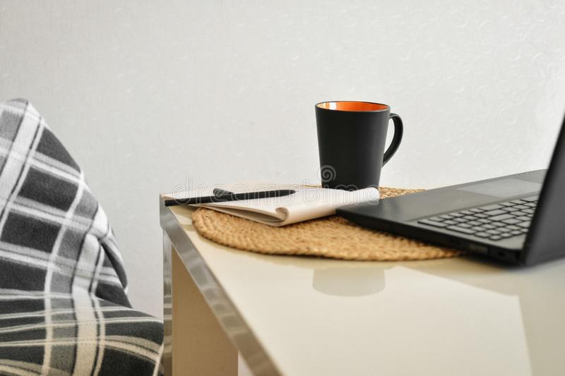 A cozy chair with a blanket and a laptop, cup of coffee, note, pen on a white kitchen table. Online shopping and freelance royalty free stock photo