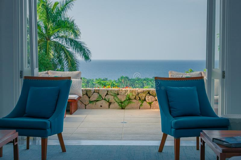 Cozy chairs inside of a beach house with open doors leading to palm trees and the ocean stock photography