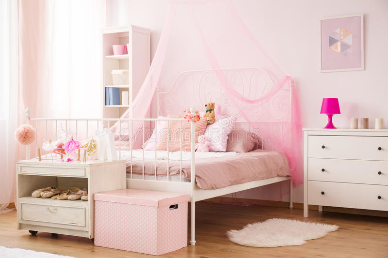 Cozy child bedroom in pink. With canopy bed and dresser royalty free stock photos