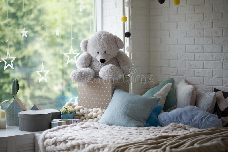 Cozy children`s room in bright soft colors, pillows and a blanket are lying on the bed stock image