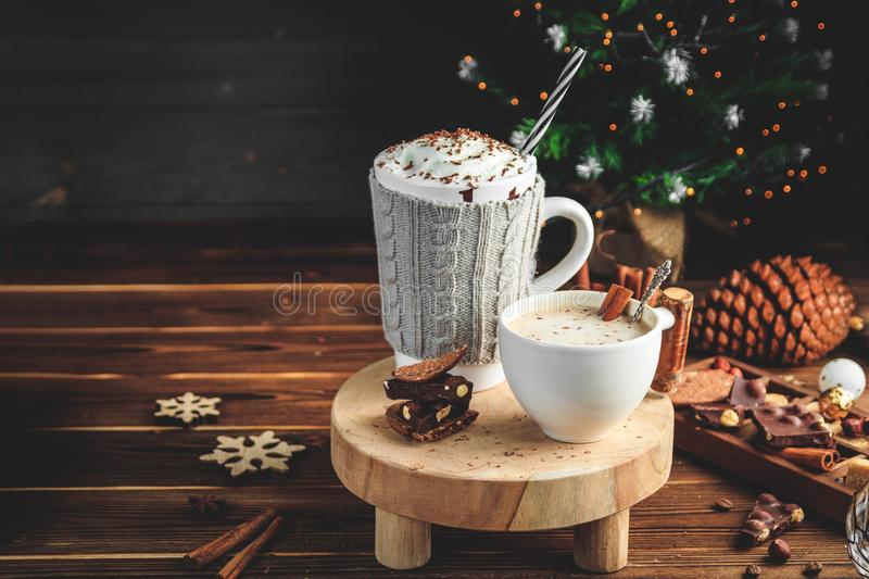 Cozy Christmas composition.Two mug with hot drinks, chocolate with whipped cream and cappuccino with cinnamon stick on a stock photos