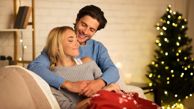 Cozy Christmas eve. Loving couple embracing near Christmas tree stock image