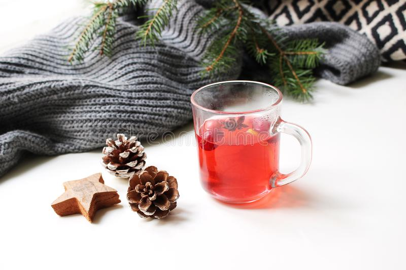 Cozy Christmas morning breakfast scene. Steaming glass cup of hot fruit tea. Pine cones, wooden stars on white table royalty free stock photo