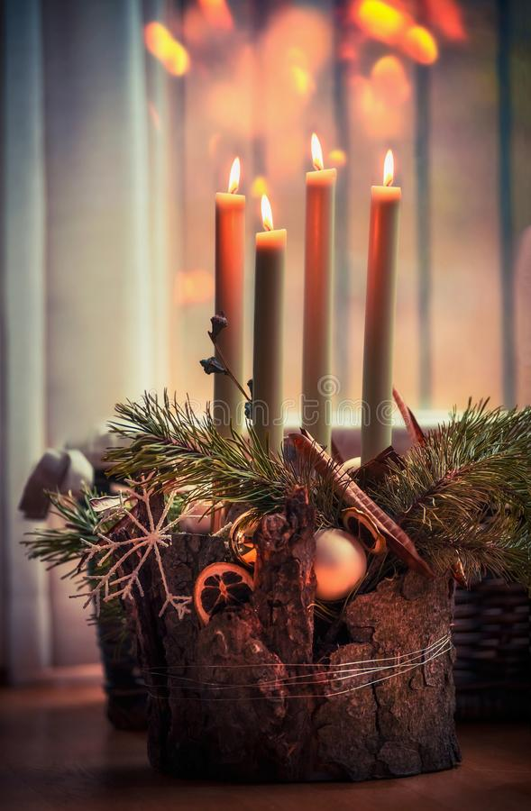 Cozy Christmas time at home. Advent wreath with four burning candles. Winter decor interior with warm bokeh lighting stock photography
