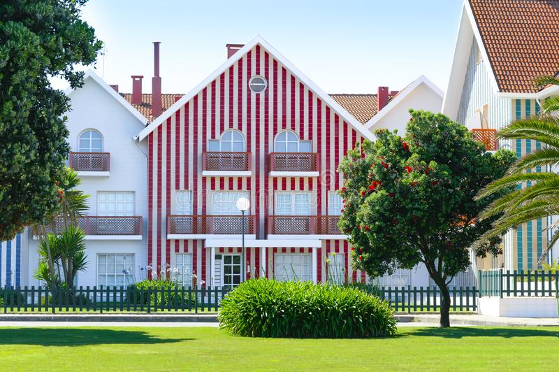 Cozy colorful striped house with red and white stripes in countryside. Lawn and blossoming tree with red flowers. Costa Nova, Portugal stock photos