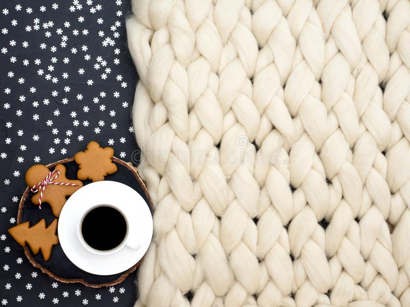 Cozy composition, closeup merino wool blanket, warm and comfortable atmosphere. Knit background. Cup of coffee and ginger cookies. royalty free stock image