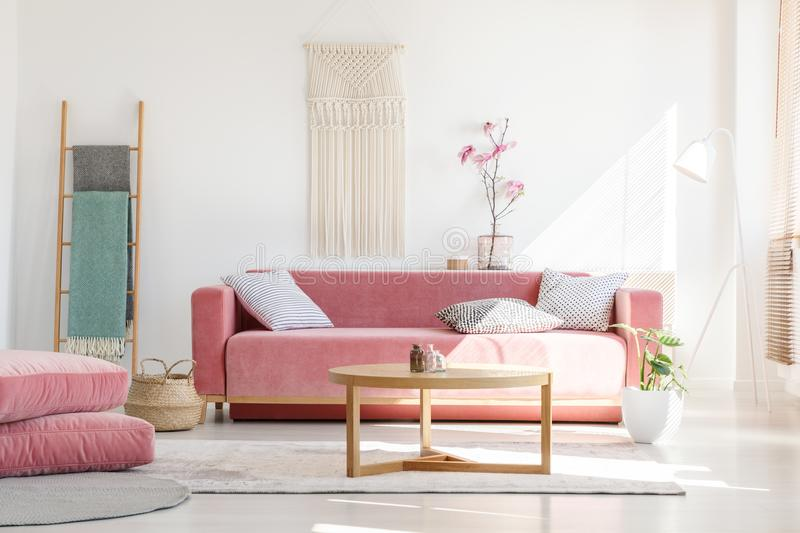 Cozy cushions and stylish textiles in a sunny, feminine living r. Oom interior with a pink, velvet sofa and a macrame on a white wall royalty free stock images